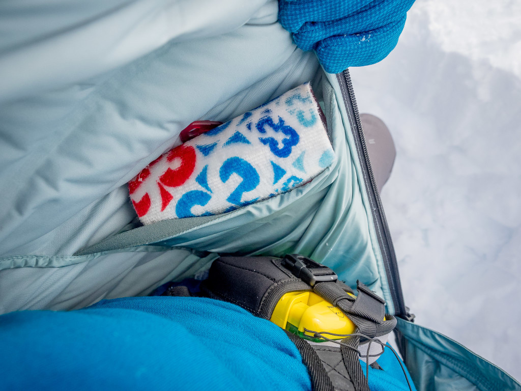 Large internal pockets being used to keep ski skins dry and warm