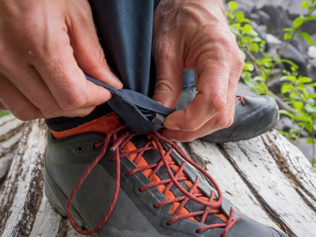 Hook to secure pants to lace on hiking boots or shoes